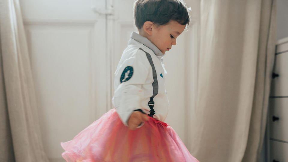 Ein kleiner Junge trägt ein rosanes Tutu