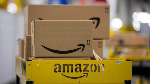 Pakete liegen in einem Logistikzentrum des Versandhändlers Amazon auf einem Wagen