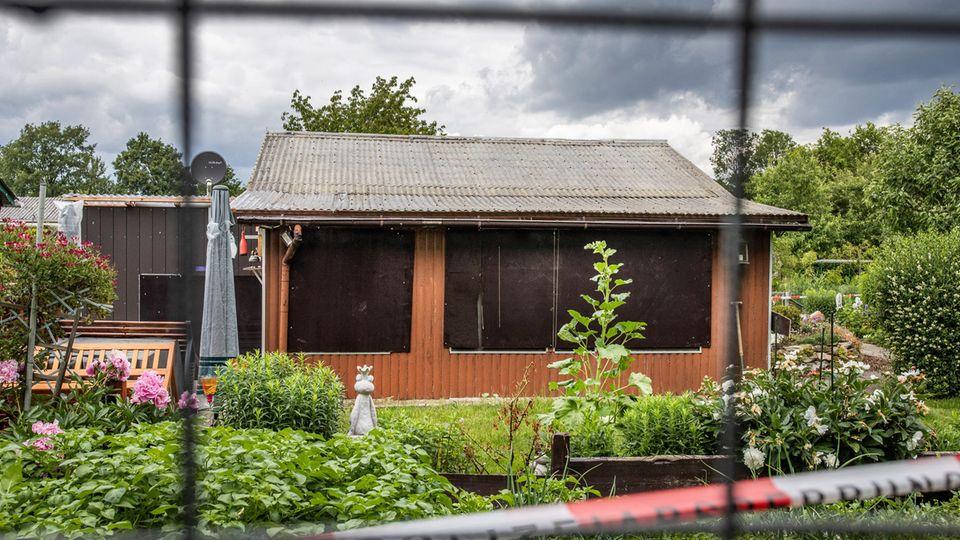 Absperrband umgibt ein Grundstück in einer Kleingartenkolonie am Stadtrand von Münster mit einer Gartenlaube