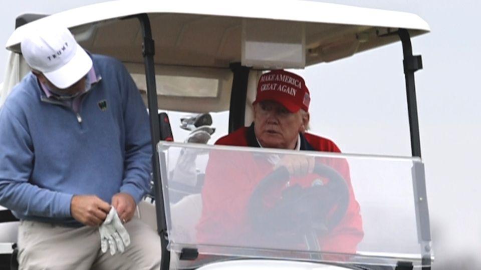 Der ehemalige US-Präsident Donald Trump sitzt im Golfwagen.