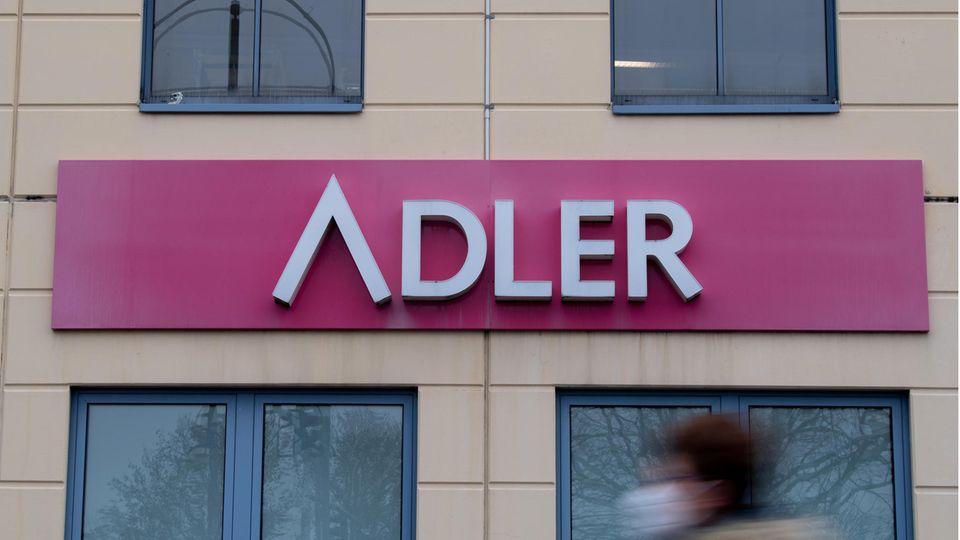 Eine Frau mit Mund-Nase-Bedeckung geht an einem Schild des Unternehmens Adler Modemärkte an einem Einkaufszentrum vorbei