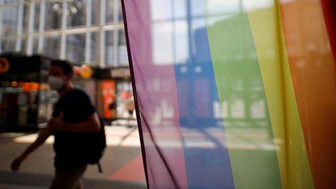 Vor dem Infoschalter der Deutschen Bahn im Kölner Hauptbahnhof stehen Regenbogenflaggen