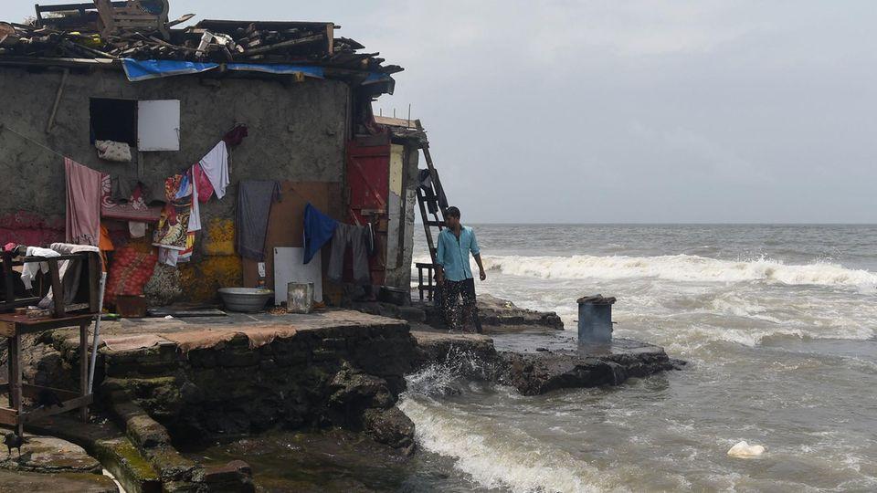 Ein Mann steht im indischen Mumbai vor seinem Haus.