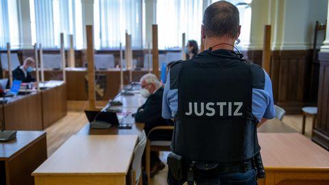 Ein Justizbeamter bewacht die Anklagebank im Landgericht Leipzig.
