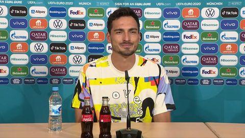 """Mats Hummels in einem bunten T-Shirt mit der Aufschrift """"Love unites"""" bei einer Pressekonferenz"""