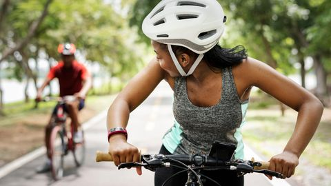 Eine Frau und ein Mann fahren Fahrrad und tragen Helme