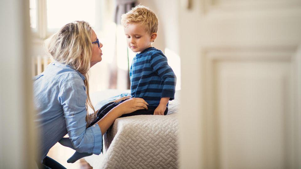 Eine junge Mutter im Gespräch mit ihrem kleinen Sohn in einem Schlafzimmer
