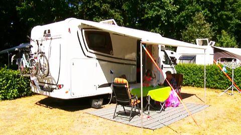 Familie sitzt vor ihrem Campingwagen