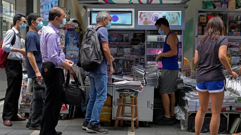 Menschen stehen Schlange vor Kiosk