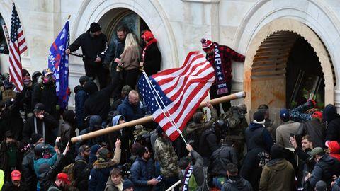 Anhänger des damaligen US-Präsidenten Trump stürmen das US-Kapitolgebäude und schwingen eine USA-Flagge
