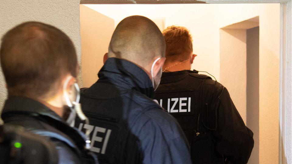 Polizisten in Uniformen betreten eine Wohnung