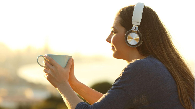 Frau hört Musik, guckt in die Sonne und trinkt aus einer Tasse