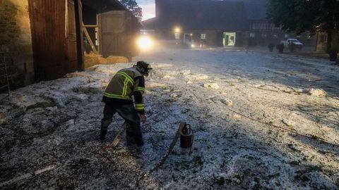 Ein Feuerwehrmann steht in einem Reiterhof in Hagelkörnern und Wasser und stellt eine Pumpe auf