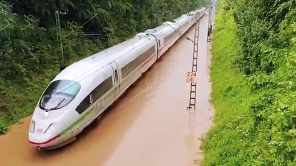 ICE fährt durch überschwemmte Bahntrasse
