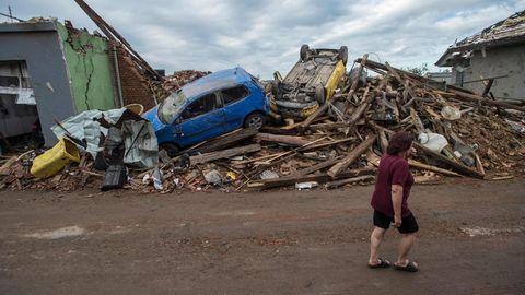 Eine Frau geht im Dorf Mikulcice in Tschechien an den Trümmern eines Haus vorbei