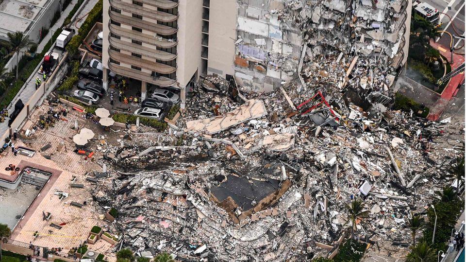 Rettungskräfte suchen in den Trümmern des eingestürzten Hochhauses nach Opfern