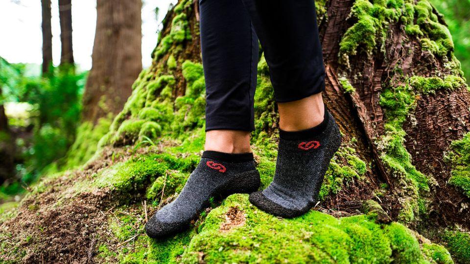Sockenschuhe im Trend: Zwei Füße mit Sockenschuhen stehen auf vermoostem Baumstamm