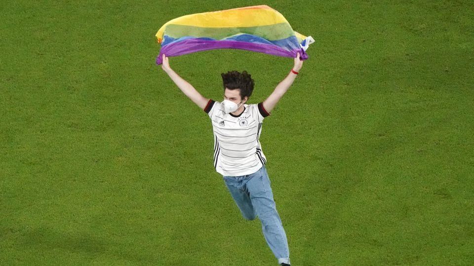 Flitzer bei der EM-Partie Deutschland - Ungarn mit einer Regenbogenflagge