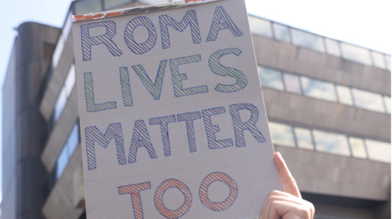 Ein Mann hält ein Pappschild hoch, auf dem Roma Lives Matter Too steht
