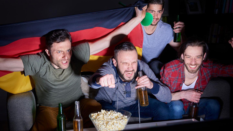 Fußball-Fans schauen sich ein Spiel im Fernsehen an und jubeln