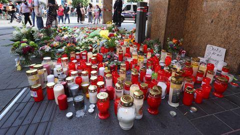 Blumen und Kerzen vor einem geschlossenen und abgesperrten Kaufhaus in der Innenstadt