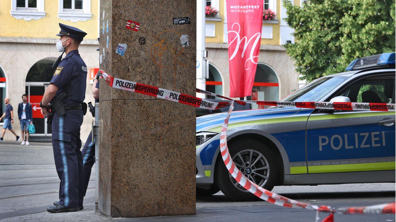 Polizisten stehen vor dem geschlossenen und abgesperrten Geschäft in der Innenstadt von Würzburg