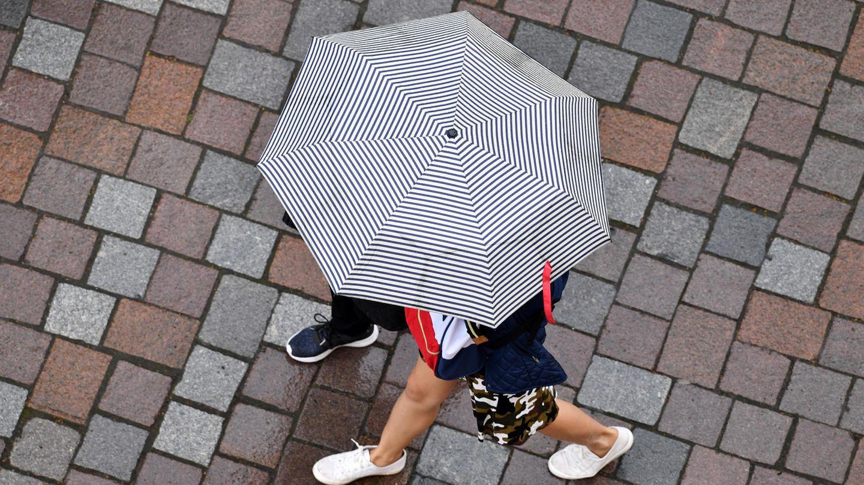 Symbolbild zum Siebenschläfer: Passanten gehen bei Regen in Potsdam spazieren.