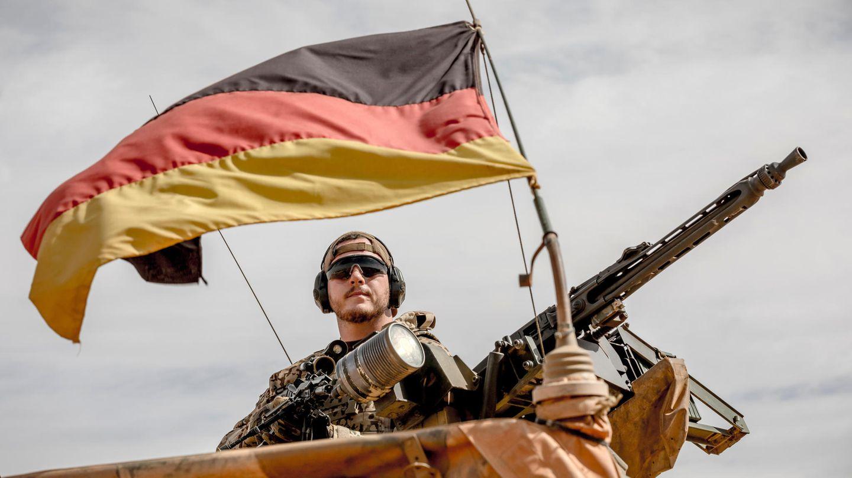Ein Bundeswehr-Soldat schaut mit Sonnenbrille und schwarzen Ohrenschützern unter einer deutschen Flagge von einem Fahrzeug herab