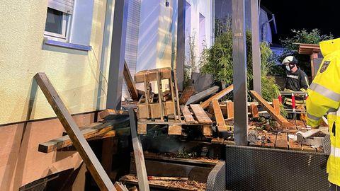 Rettungskräfte stehen neben den Trümmern eines Balkons aus Holz, der mit mehreren Menschen darauf eingestürzt ist.