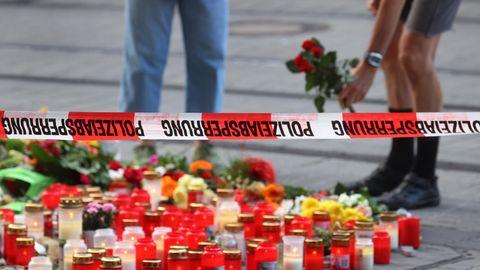 """Unter einem Flatterband mit """"Polizeiabsperrung""""-Aufdruck stehen Kerzen und liegen Blumen, zwei Menschen stehen im Hintergrund"""