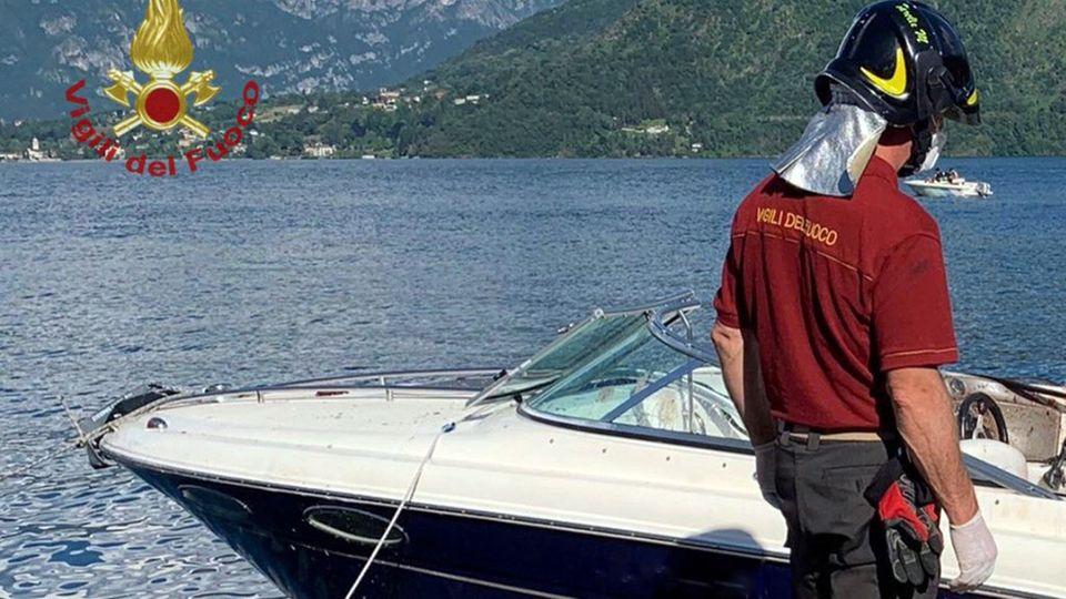 Ein Feuerwehrmann steht neben einem Motorboot, dass auf dem Comer See verunfallt war