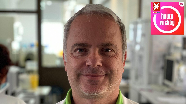 Ein weißer Mann mit grau-weißem Seitenscheitel steht in weißem Kittel in einem Labor und lächelt