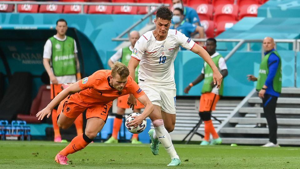 Ein Fußballer in orangem Dress greift im Fallen mit links nach dem Ball