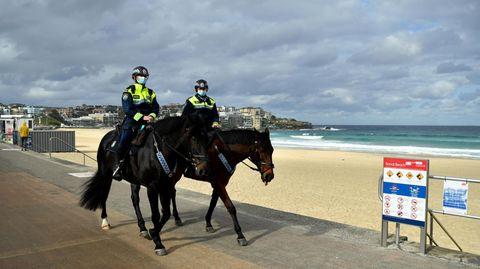 Zwei Polizisten auf Pferden reiten auf einer betonierten Strand-Promenade. Sie tragen Mund-Nasen-Schutz