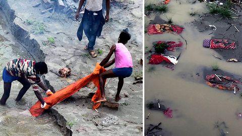 In Indien legt der Monsunregen die provisorischen Gräber am Ufer des Ganges frei