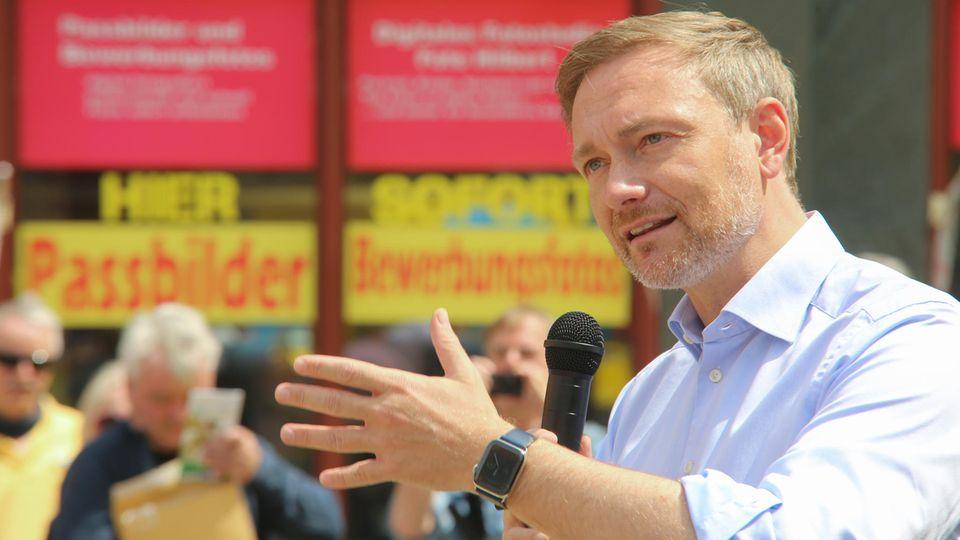 Christian Lindner mit Mikrofon in Erklärerpose vor rot-gelben Aufklebern