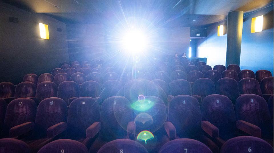 Ein Kinosaal erleuchtet vom Licht des Projektors.