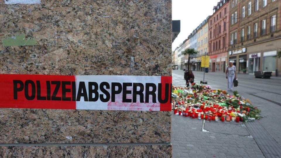 Blumen und Kerzen stehen in Würzburg vor einem Kaufhaus, im Vordergrund ist ein Absperrband der Polizei zu sehen
