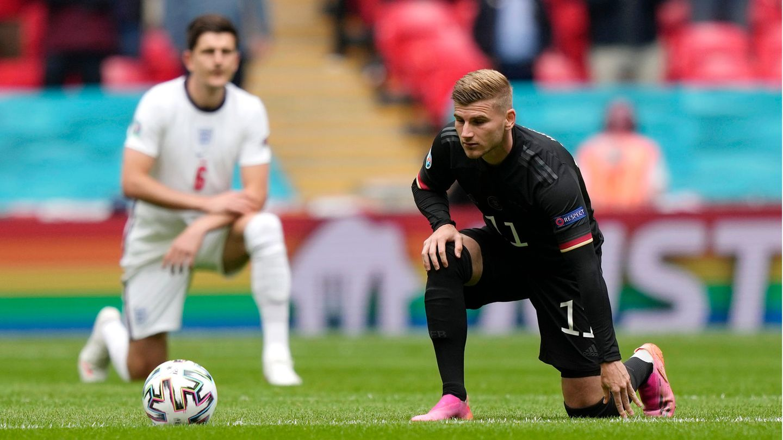 Ein blonder Fußballer im schwarzen Dress des DFB-Teams kniet mit links auf dem Rasen