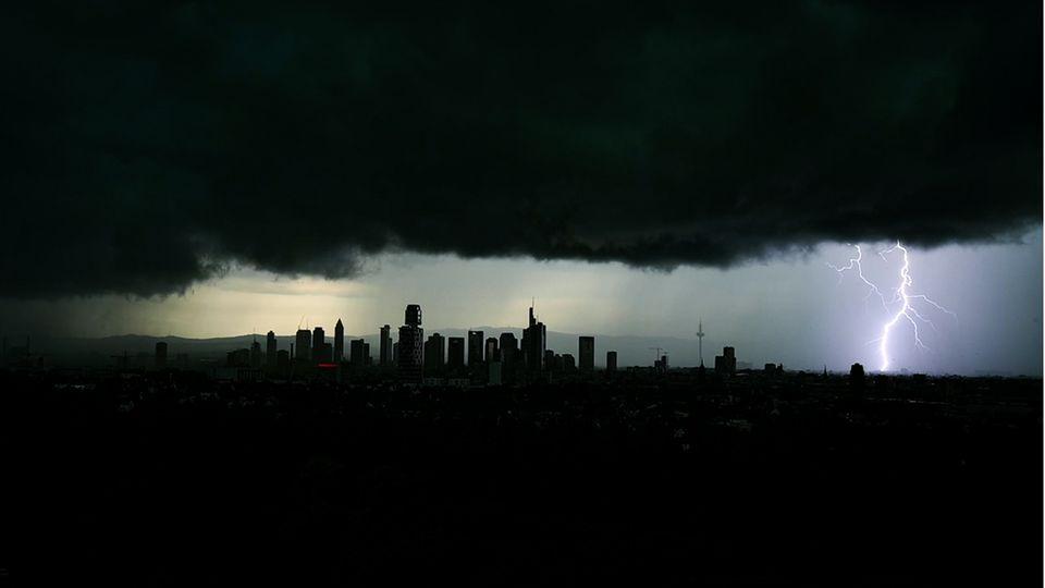 Tiefschwarze Gewitterwolken verdunkeln den Himmel über der Frankfurter Innenstadt, während sich ein Blitz entlädt