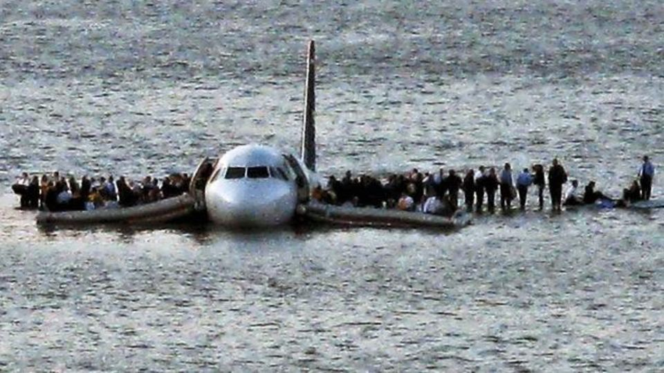 Airline passengers wait to board a ferry to be rescued on the wings of a US Airways Airbus 320 jetliner that safely ditched in the frigid waters of the Hudson River in New York, Thursday Jan. 15, 2009 after a flock of birds knocked out both its engines....