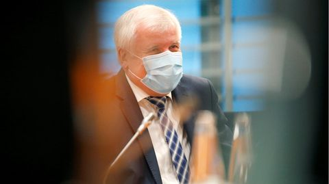 Horst Seehofer sitzt mit einer Maske im Sitzungssaal