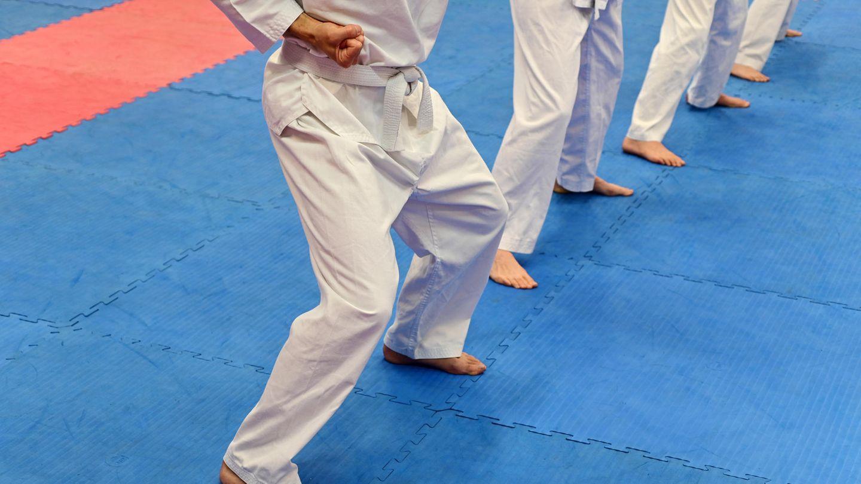 Gruppe von nicht erkennbaren Personen, die Kampfsport auf einer Sportmatte üben