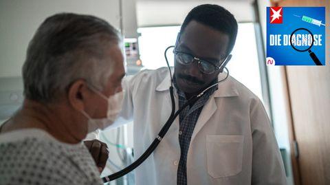 Ein Arzt untersucht einen älteren Mann mit Stethoskop