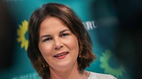 Eine weiße Frau mit dunkelbraunen, schulterlangen Haaren steht an einem Mikrofon or einer grünen Wand mit Sonnenblumen darauf