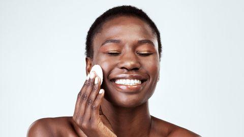 Eine Frau reinigt mit einem Wattepad ihr Gesicht