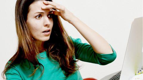 Eine Frau schaut auf ein Laptop und greift sich an den Kopf