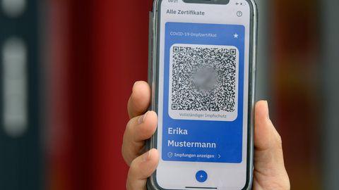 Eine Hand hält ein Mobiltelefon mit einem QR-Code
