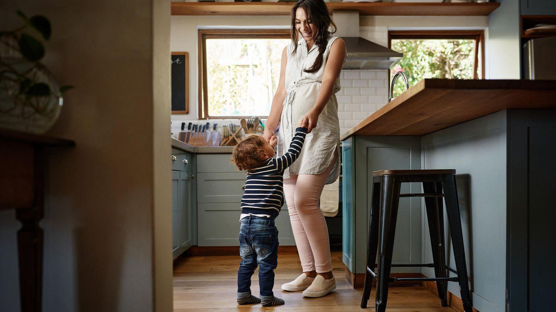 Eine Mutter spielt in der Küche mit ihrem Kleinkind