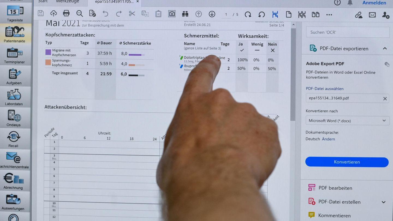 Eine Hand zeigt auf Eintragungen auf einem Computerbildschirm